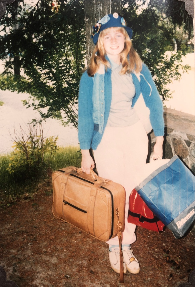Young teenager dressed for camping, standing outdoors, smiling and holding luggage